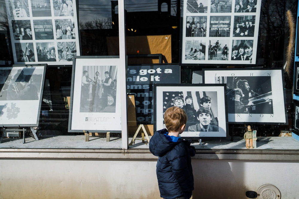 A little boy looks at a picture of the Beatles in a store window.