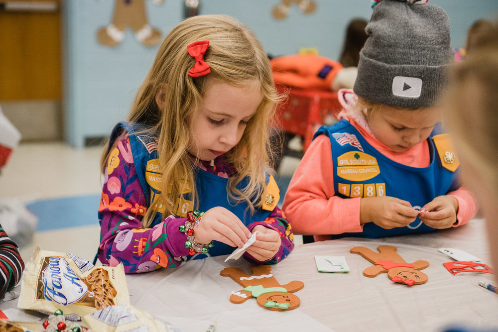 Girl Scouts sit at a table and make Christmas crafts.