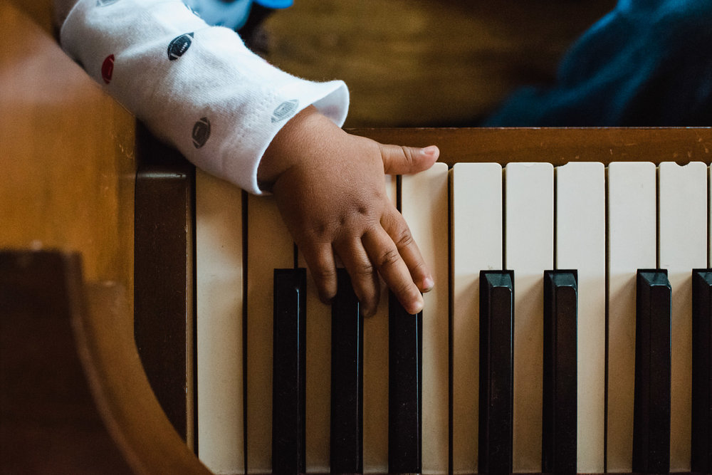 A small hand plays with piano keys.