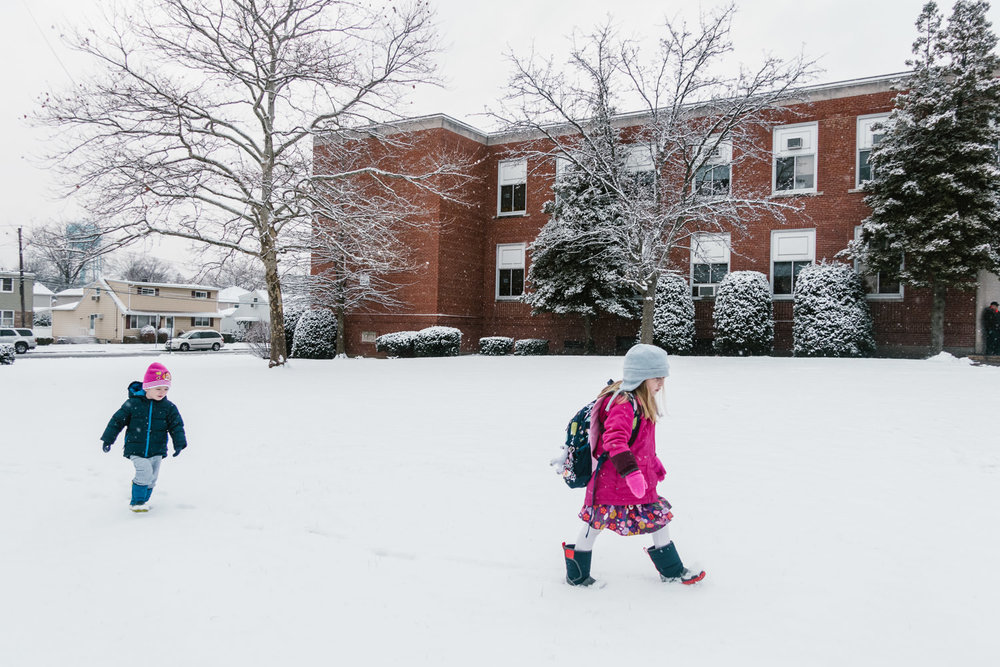 Two kids walk to school in the snow in Franklin Square, NY.