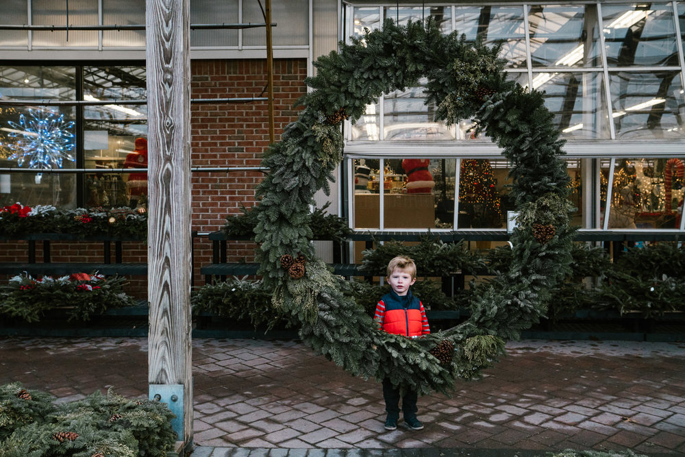 A little boy stands behind a big wreath at Hicks' Nursery.
