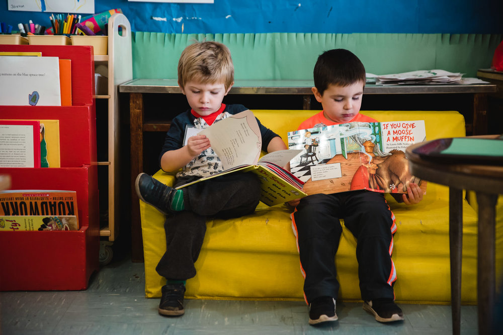 Two boys read books at nursery school.