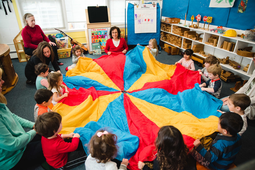 Kids play with a parachute at nursery school.