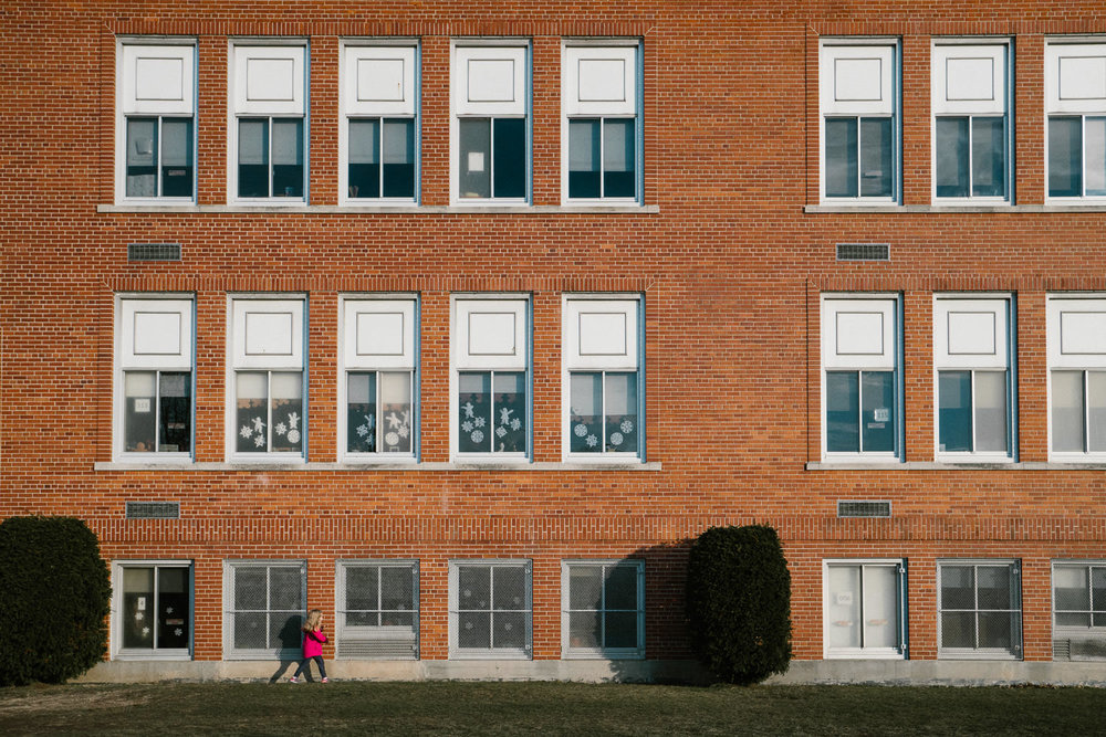A little girl walks by an elementary school building.