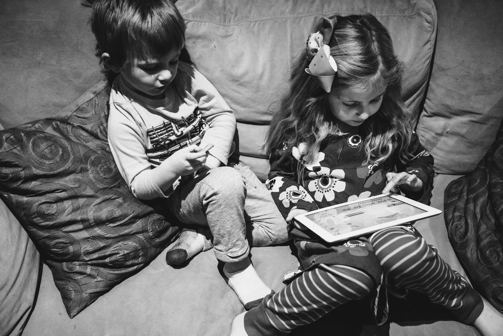 Two kids play with an iPad on the couch.