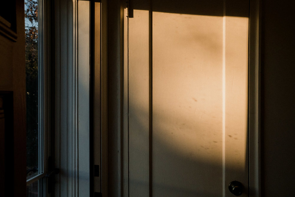 Afternoon light shines on a closet door.