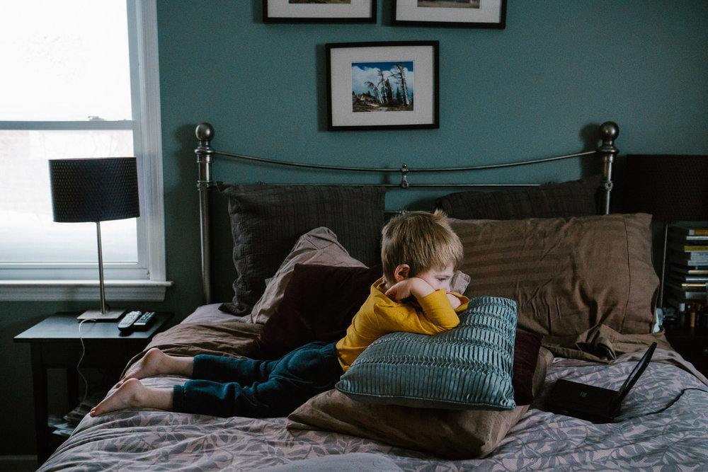A little boy watches an iPad on his parents' bed.