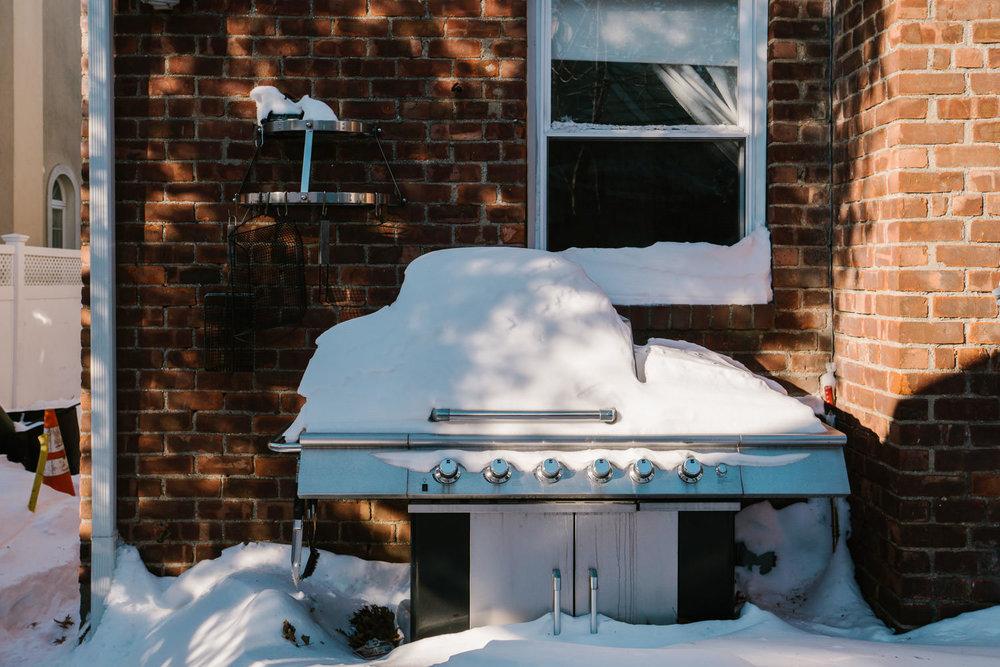 A snowy backyard grill.