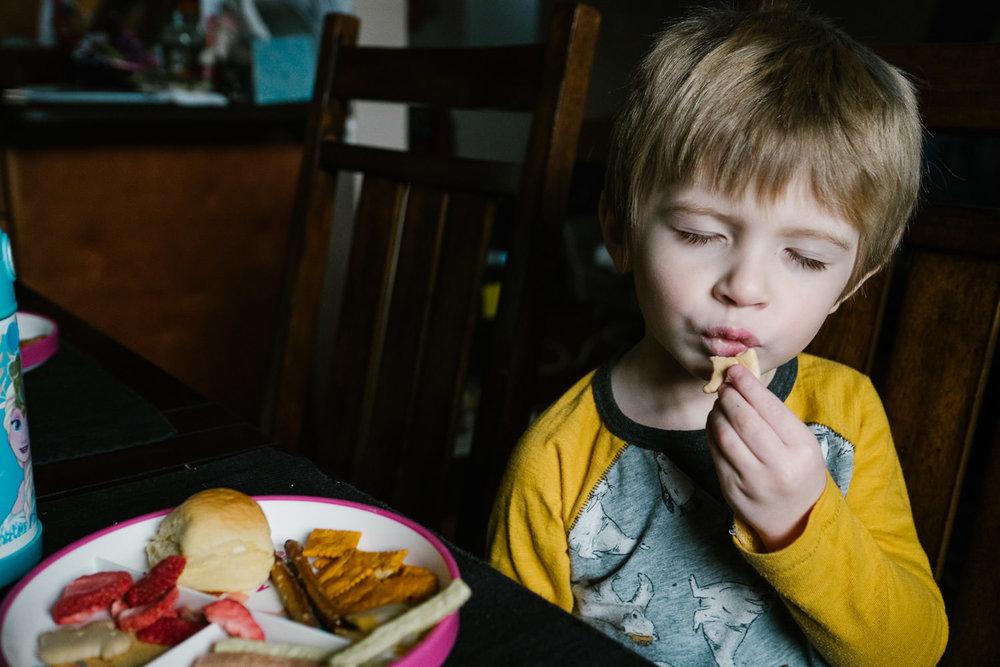 A little boy enjoys his lunch.