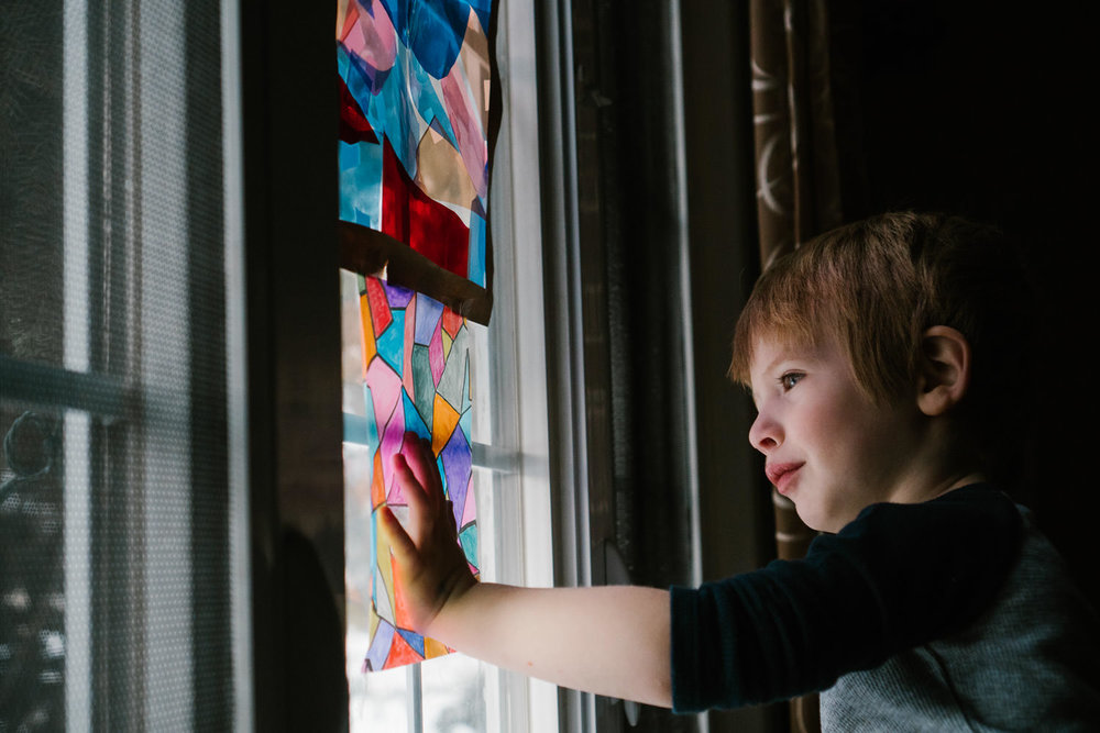 A little boy looks out a window with colored paper taped to it.