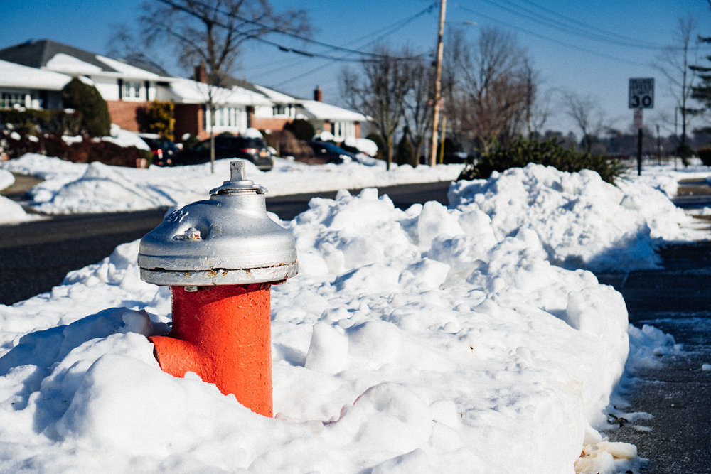 A fire hydrant buried in snow.