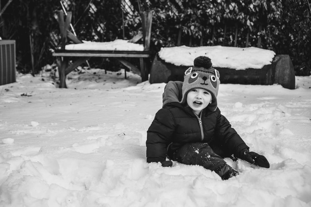 A little boy plays in the snow.
