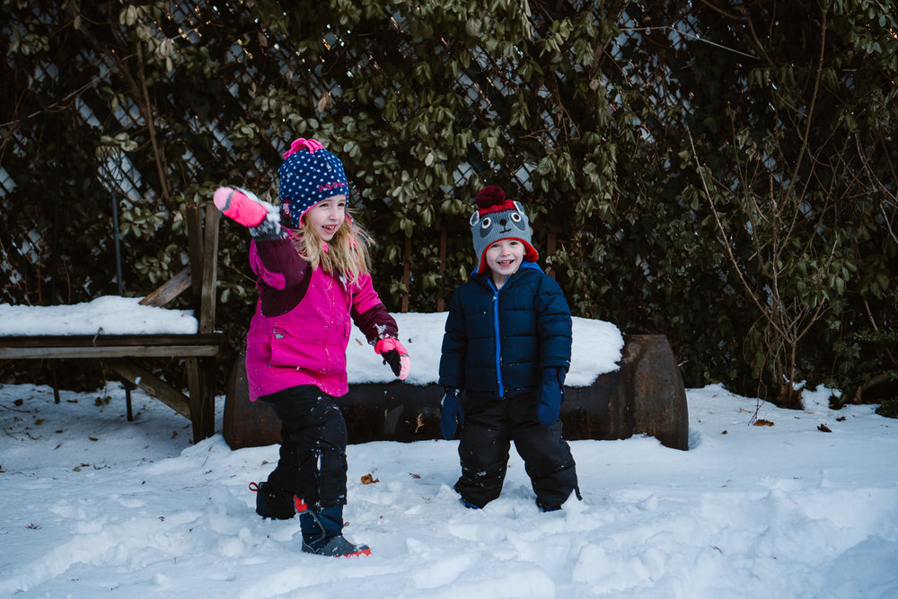 Two kids throw snowballs in their backyard.
