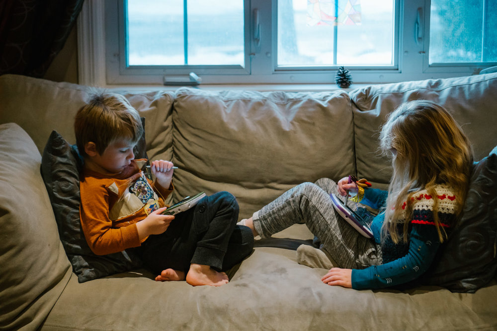 Kids play with tablets on the couch.