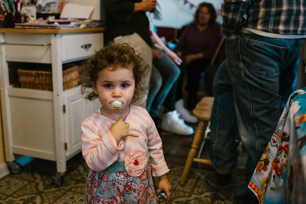 A little girl with a pacifier stands in the kitchen.