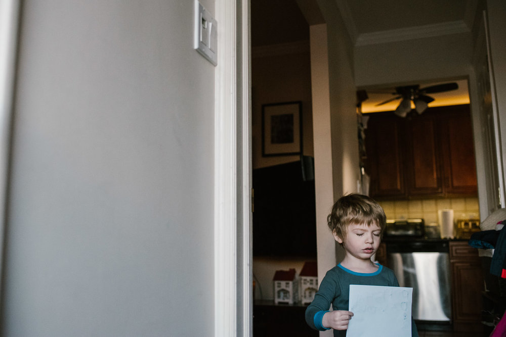 A little boy holds a piece of paper in his hallway.