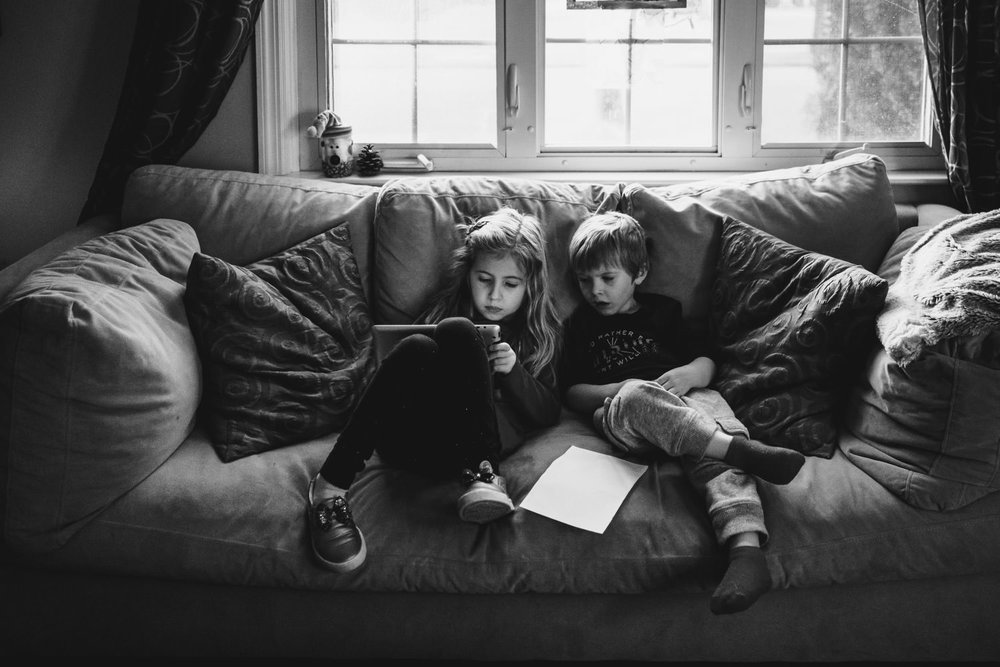 Kids play with an iPad on their couch.