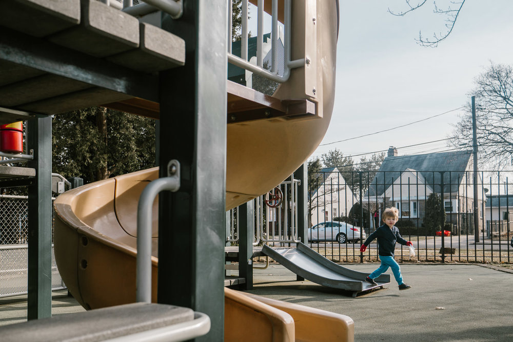 A boy runs past a slide at the playground.