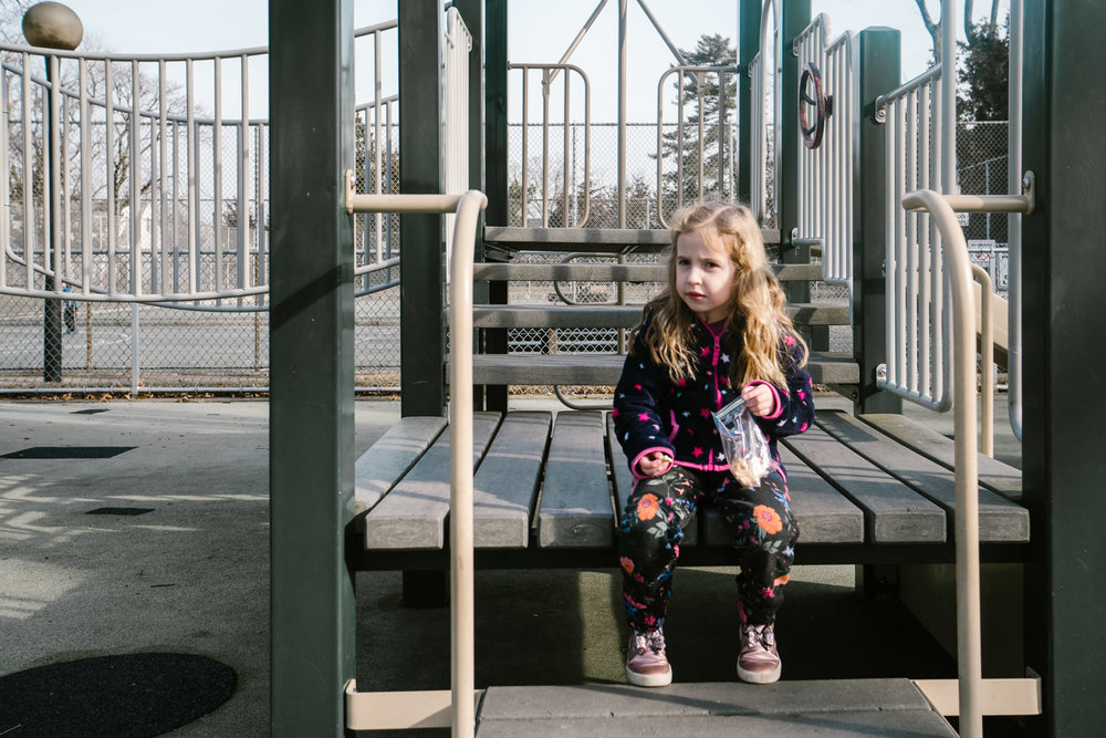 A little girl sits on a playground structure.