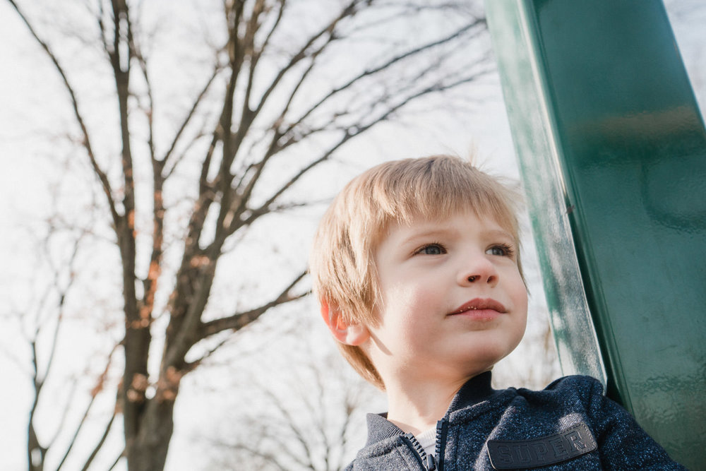 A portrait of a little boy with a tree behind him.