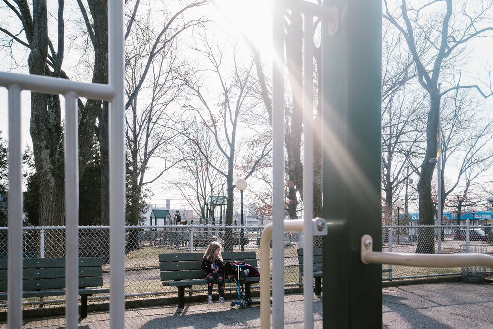 A little girl sits on a bench at the park.