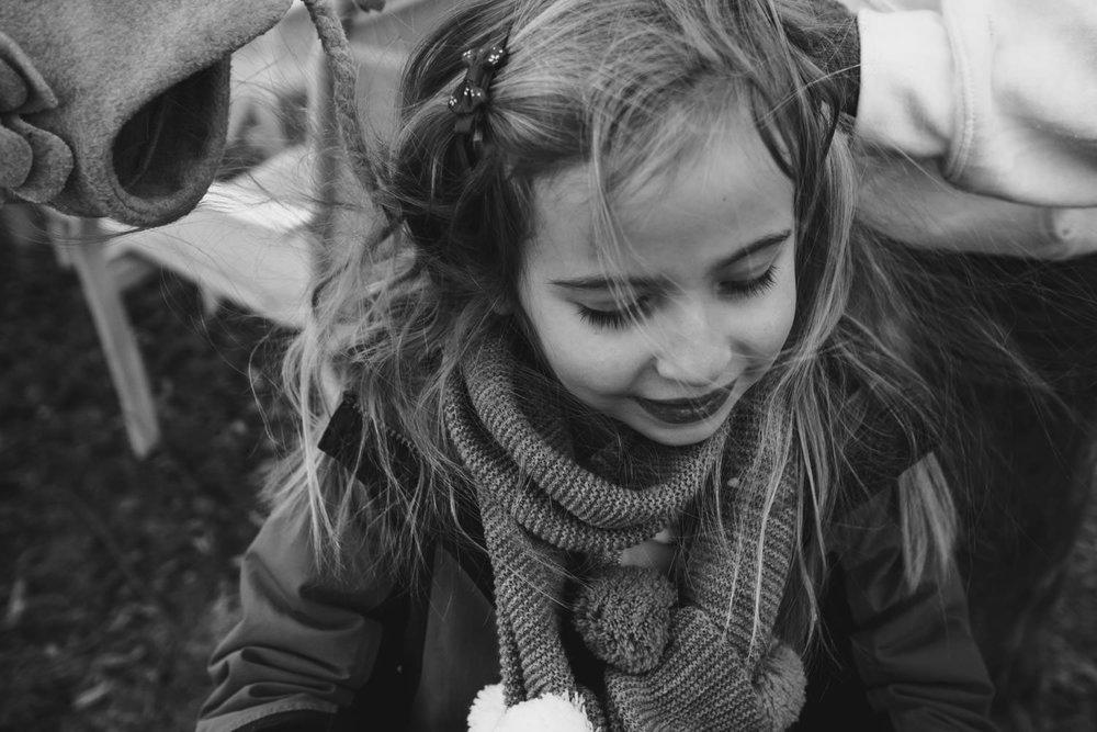 A little girl bundled up outside.
