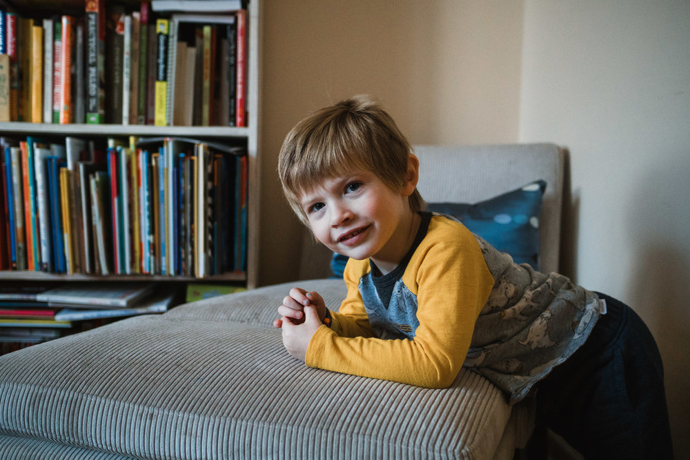 A little boy leans on an ottoman and smiles.