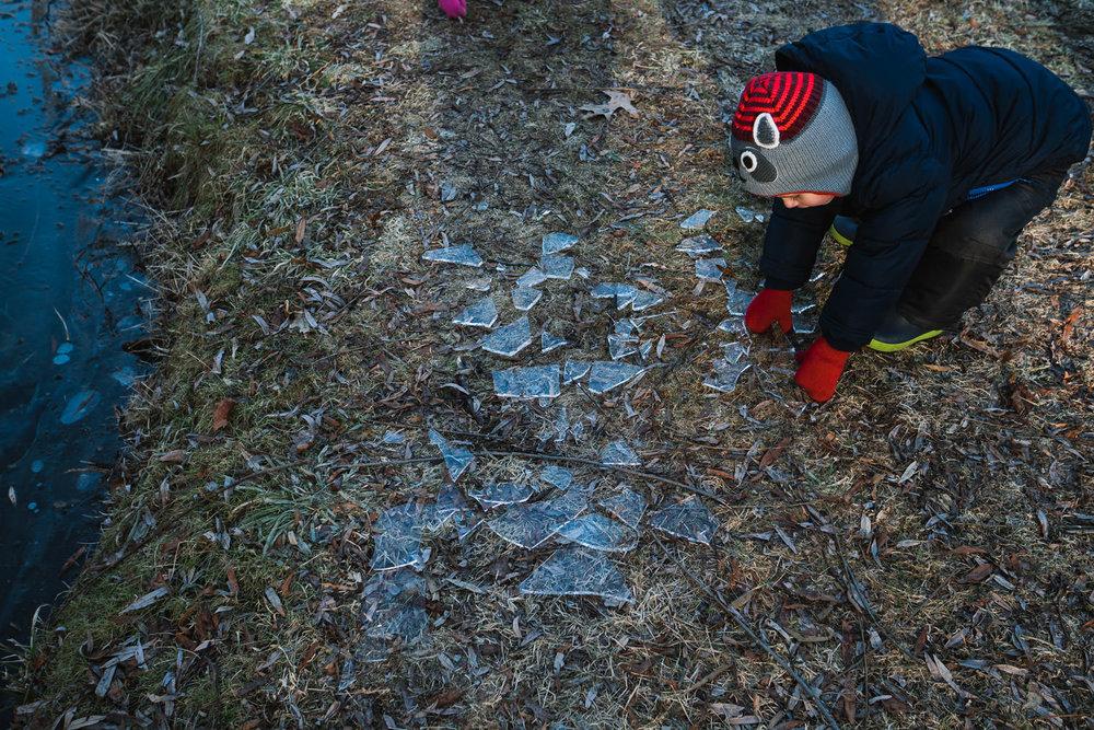 A little boy picks up some broken ice.