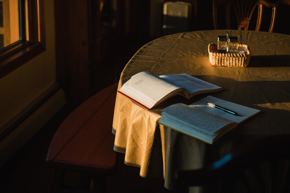 A book and journal sit in warm morning light on a table.