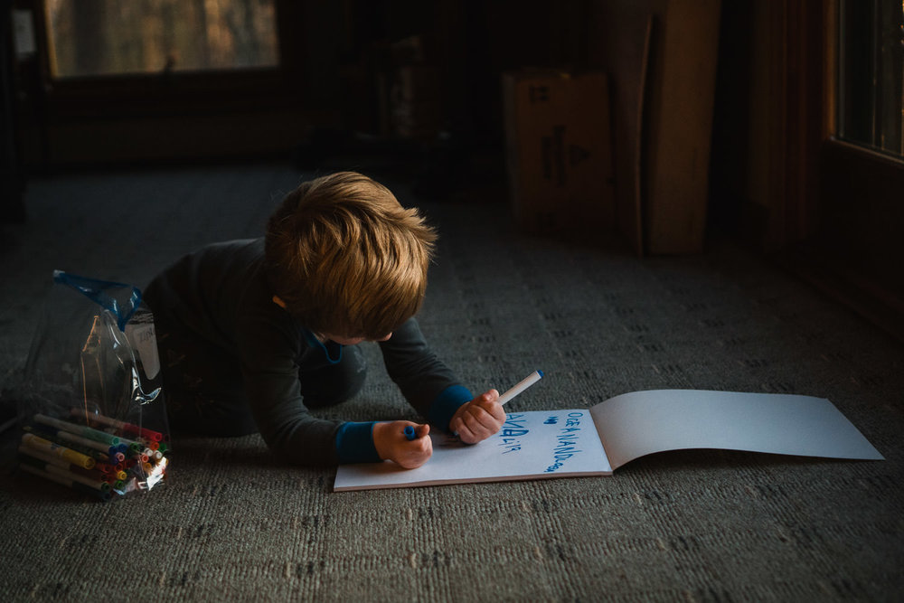 A little boy draws in a notepad on the floor.