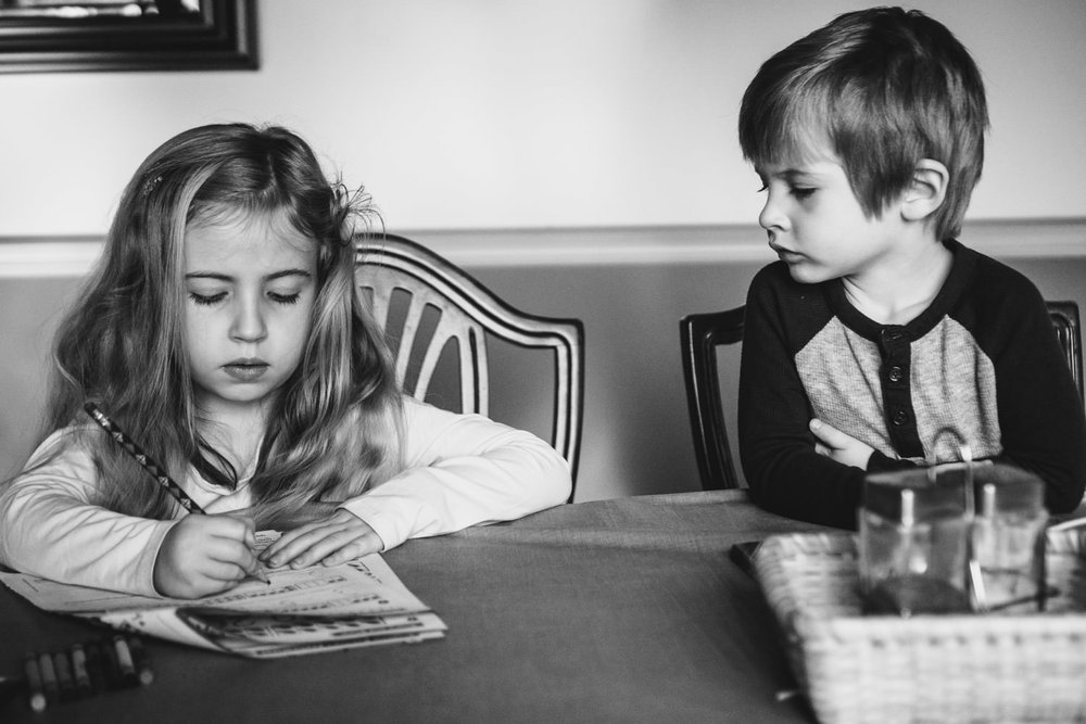 A boy and girl sit and color at a table.