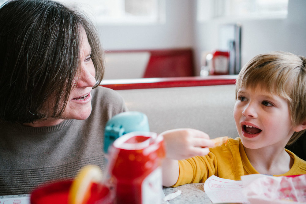A boy and his grandmother eat lunch at a diner.
