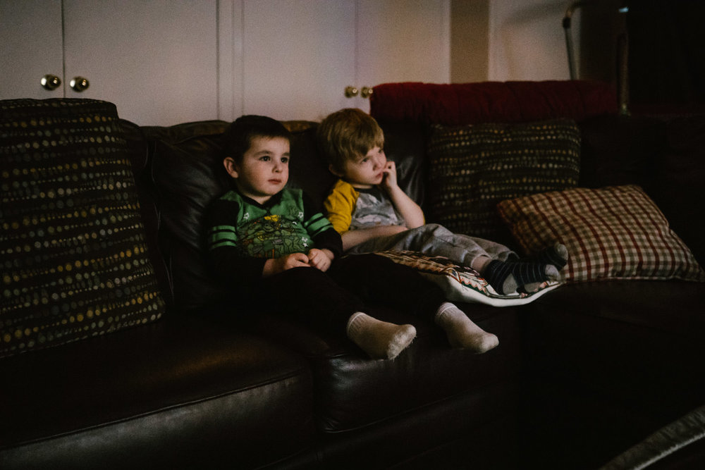 Two little boys sit on a couch and watch a movie.