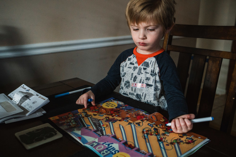 A little boy colors at his kitchen table.