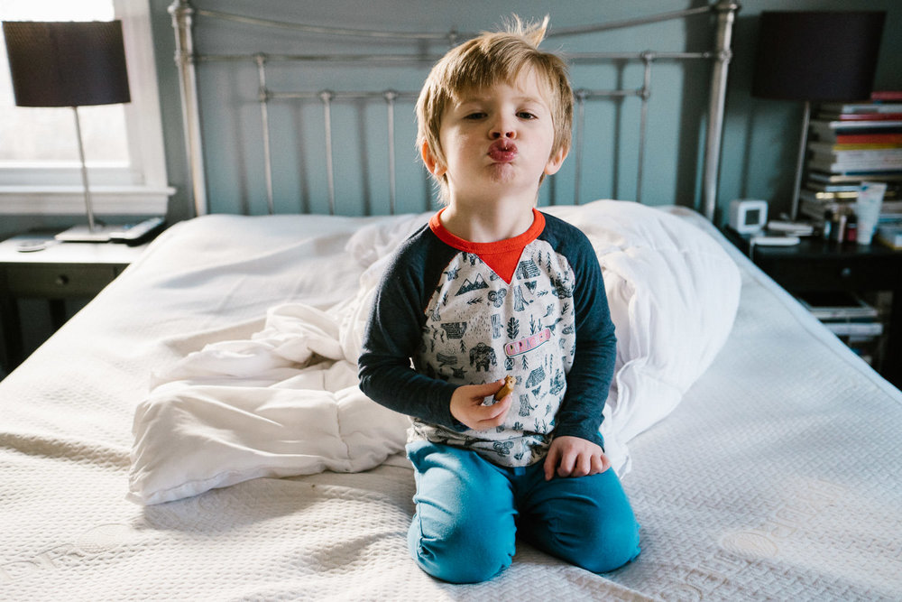 A little boy makes a kissy face at the camera, sitting on his parents' bed.