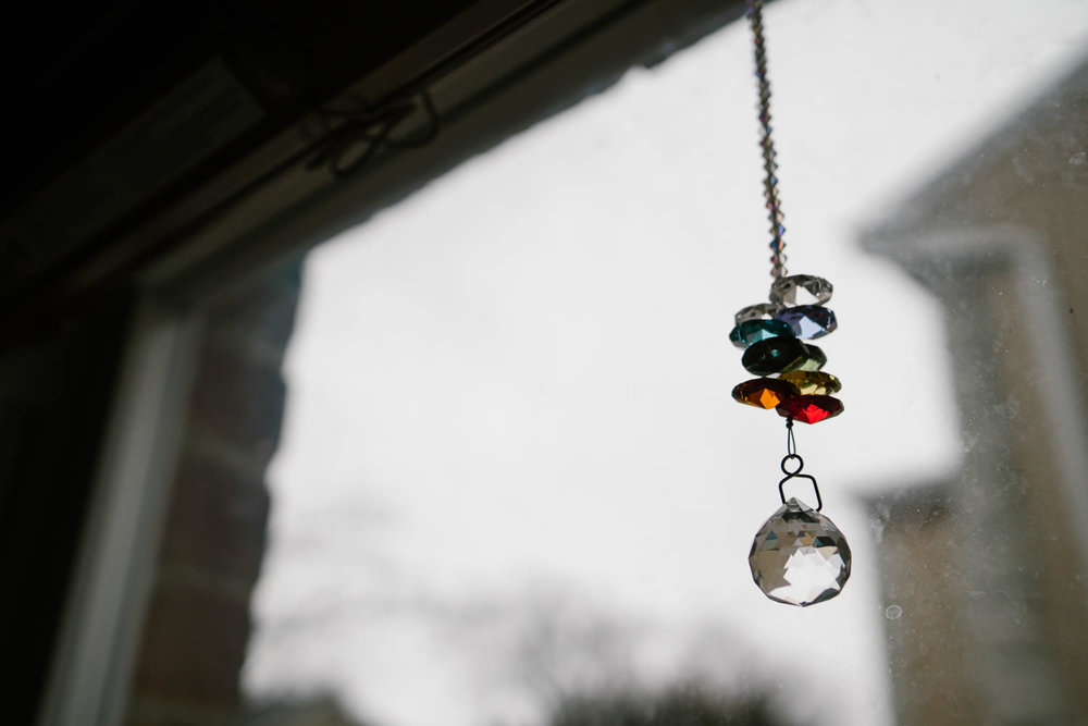 A rainbow colored prism hangs in a window.