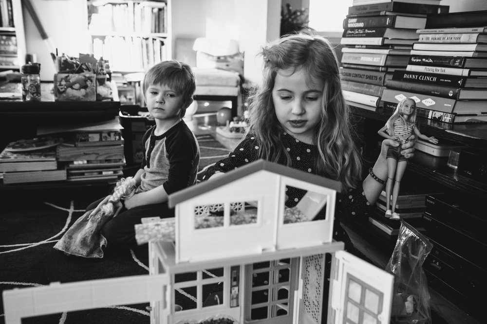 Two children play with a Barbie dollhouse.