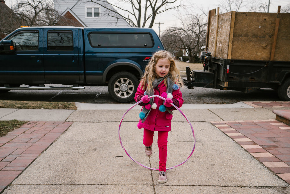 A little girl plays with a hula hoop in her driveway.