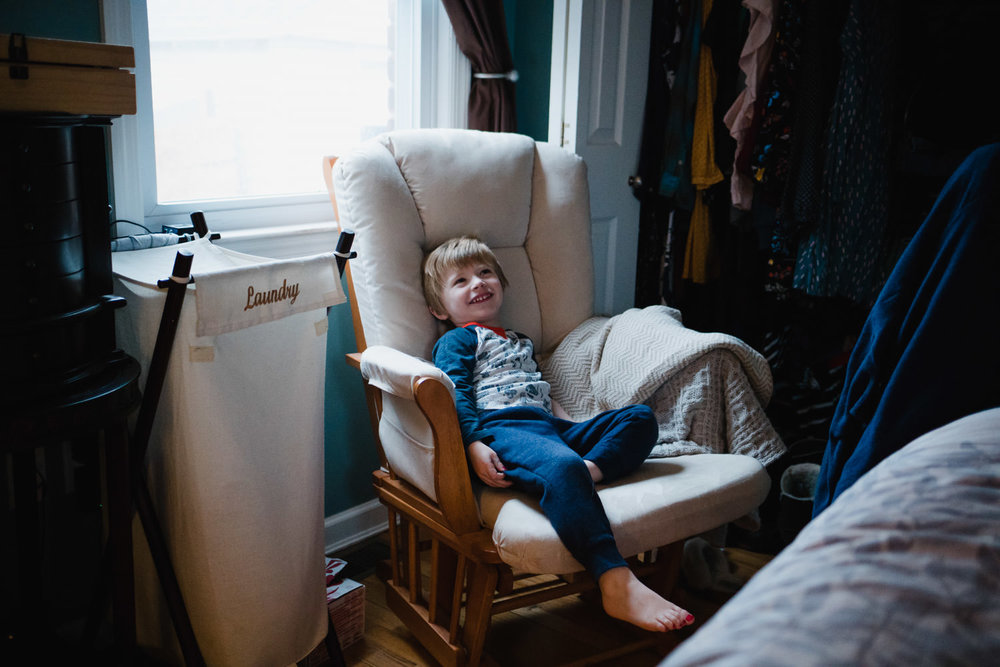 A little boy sits in a rocking chair in his parents' room.