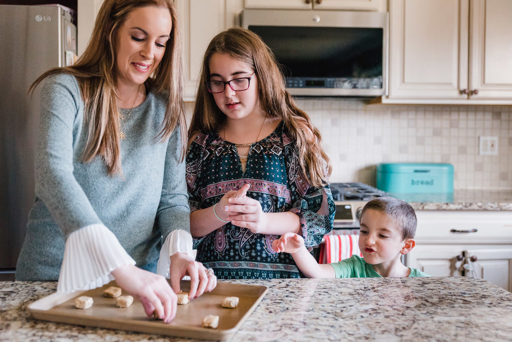 A mother bakes cookies with her two children.