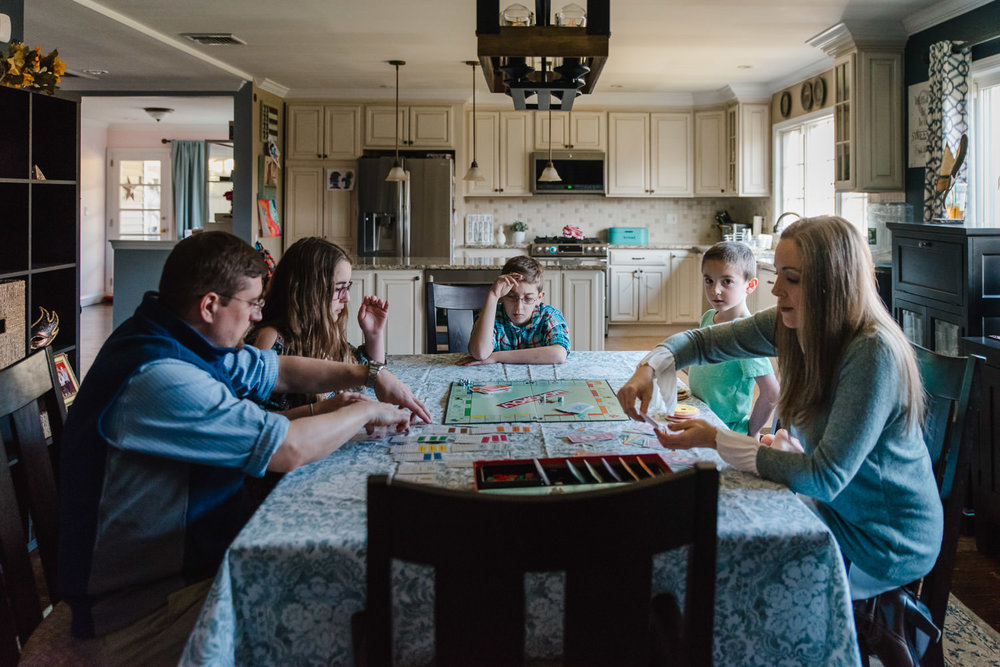 A family plays a board game at their dining room table.