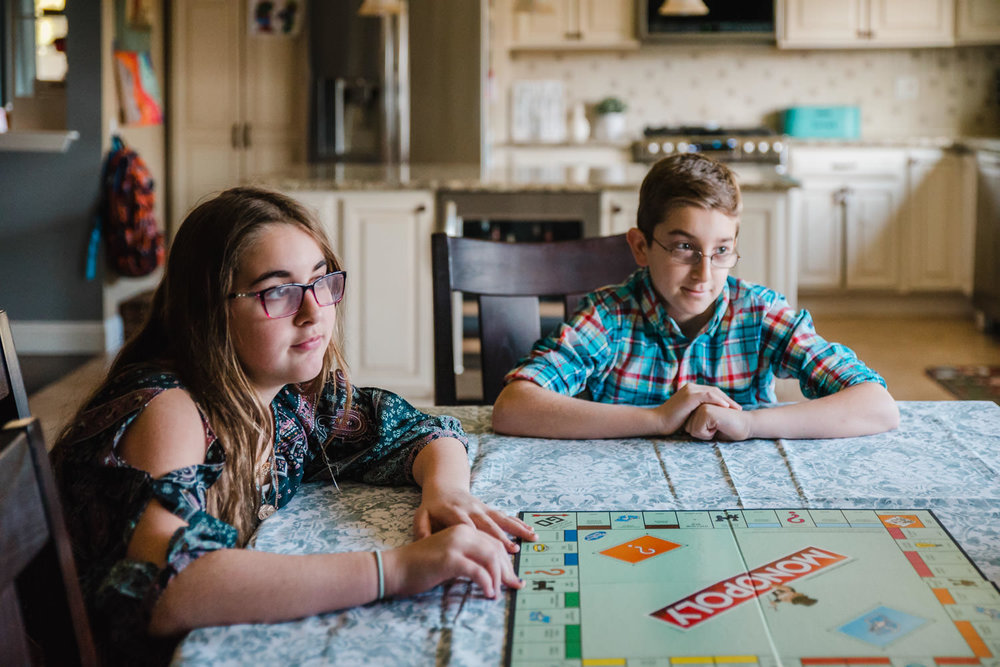 Two siblings play monopoly together.