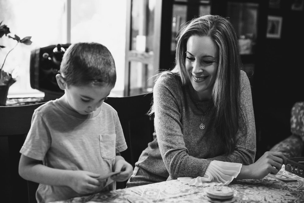 A mother helps her young son play Monopoly.
