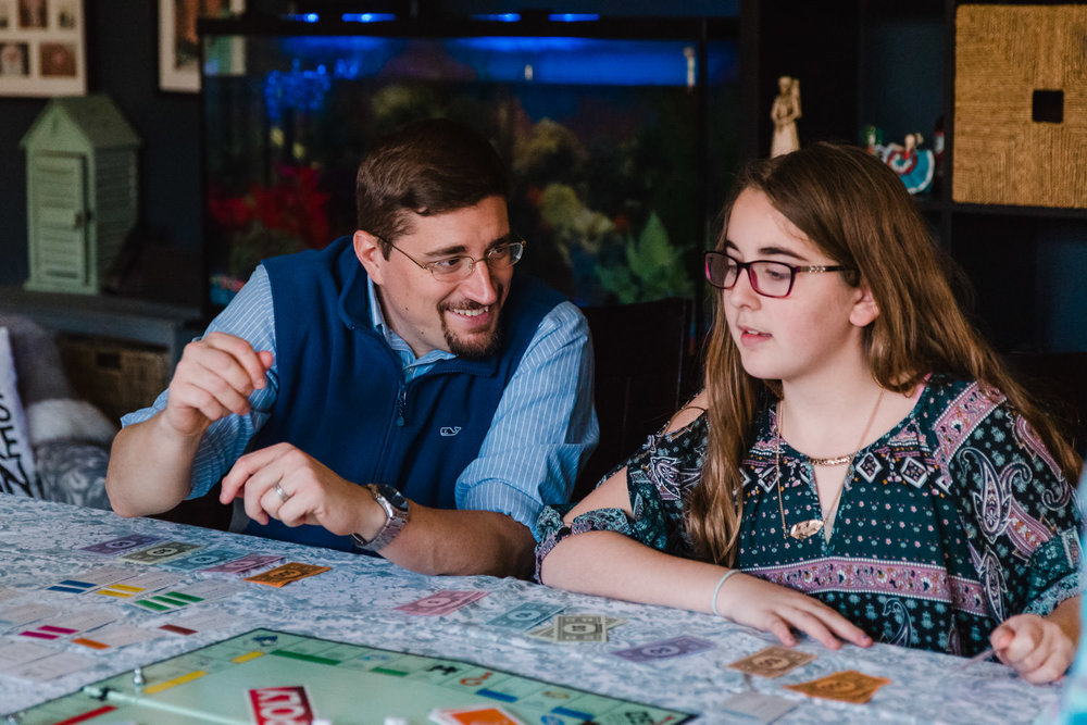 A father smiles at his daughter during a game of Monopoly.