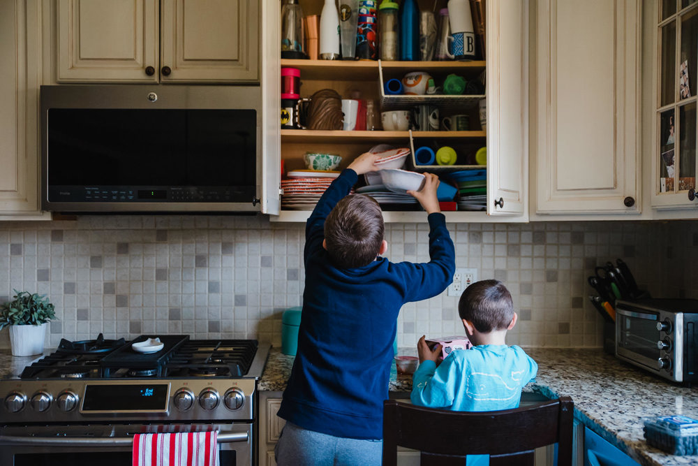 Two boys get items down from a kitchen cabinet.
