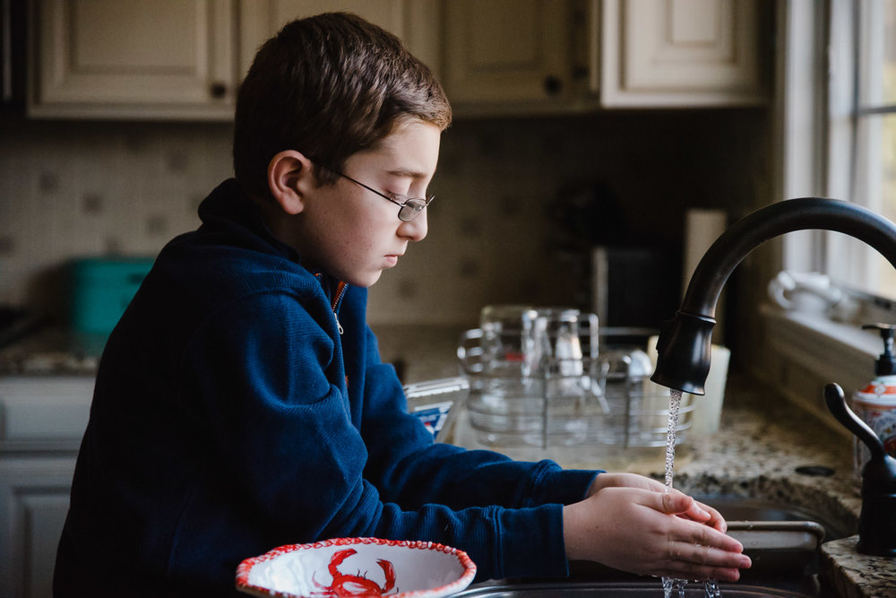 A boy washes blueberries at the kitchen sink.