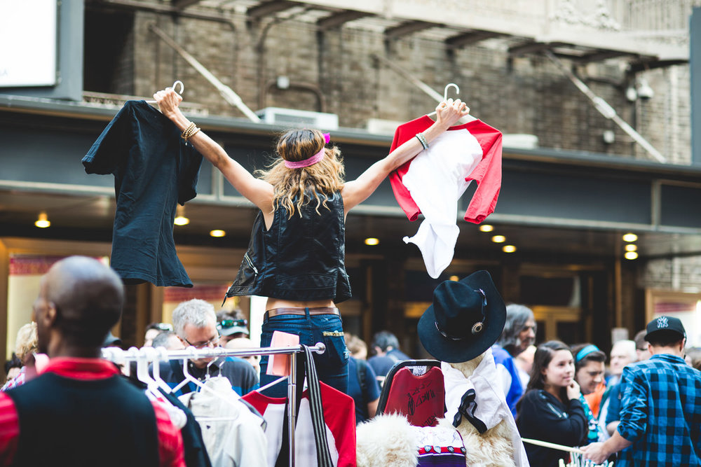A woman auctions off t-shirts at the Broadway Flea Market