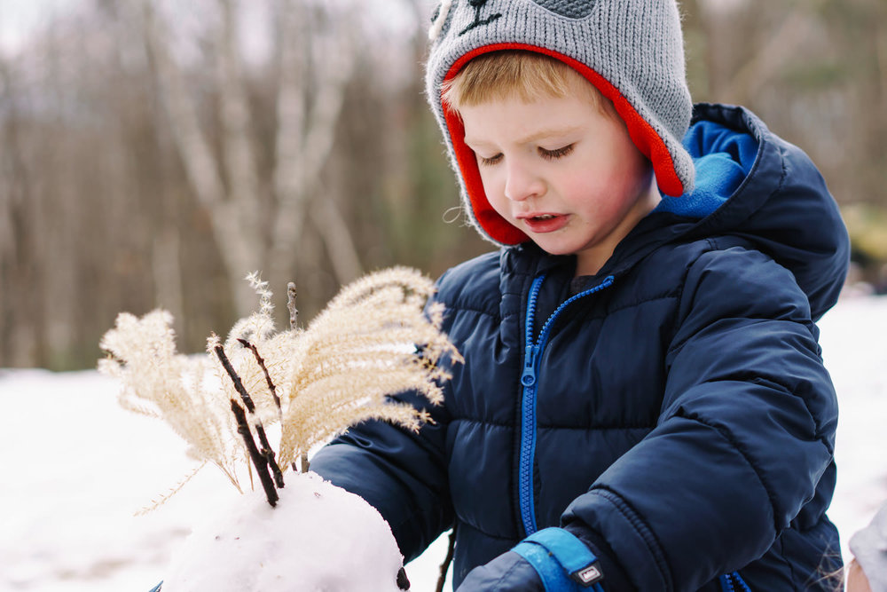 A little boy builds a snowman.