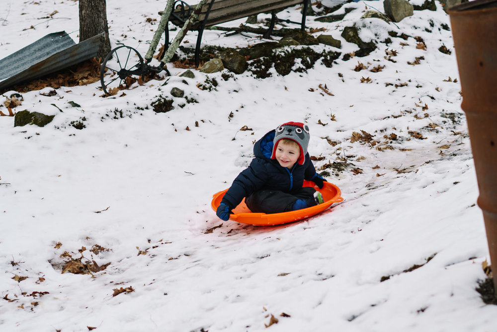 A little boy sleds down a hill.