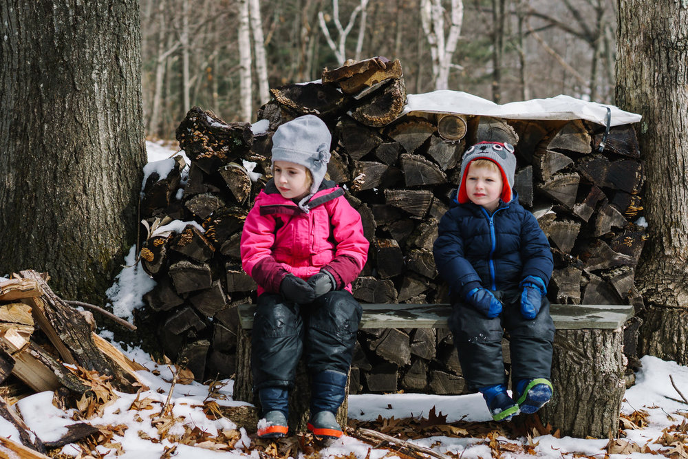 Two kids bundled up for the winter sit in front of a wood pile.